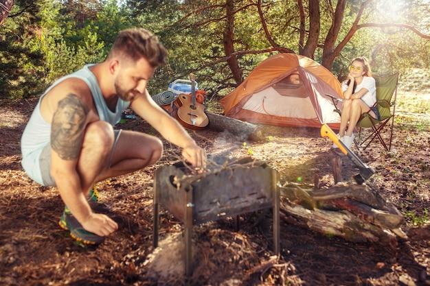 Partij, kamperen van mannen en vrouwengroep bij bos. ze ontspannen tegen groen gras. het concept vakantie, zomer, avontuur, levensstijl, picknick Gratis Foto
