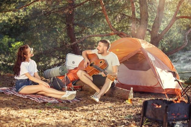 Partij, kamperen van mannen en vrouwengroep bij bos. ze ontspannen zich, zingen een lied tegen het groene gras. concept Gratis Foto