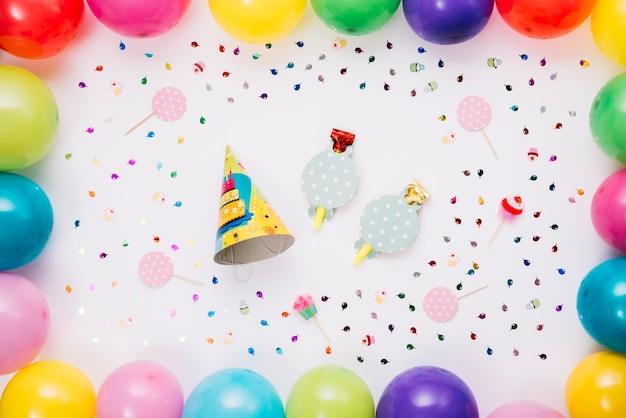 Partijhoed en hoornblazer met kleurrijke die ballons en confettien wordt op witte achtergrond worden geïsoleerd verfraaid die Gratis Foto