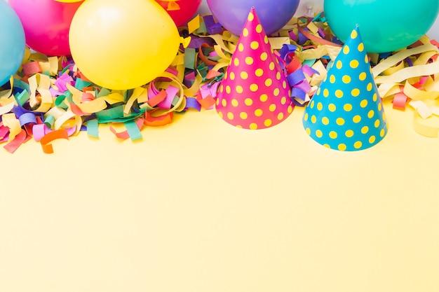 Partijhoeden dichtbij ballons op confettien Gratis Foto