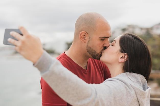 Partners die kussen terwijl het nemen van selfie Gratis Foto