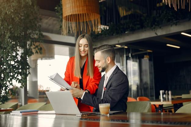 Partners zitten aan de tafel en werken in een café Gratis Foto