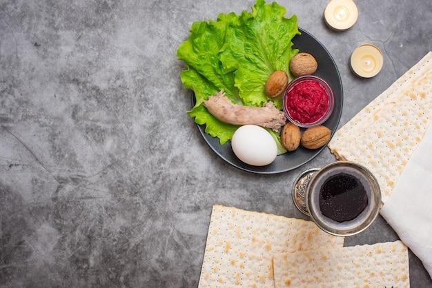 Pascha achtergrond met wijn, matza en seder plaat op grijs. Premium Foto