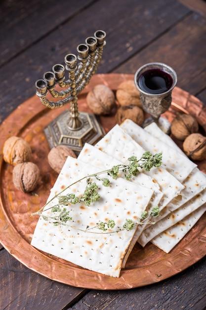 Pascha, het feest van ongezuurde broden, matza-brood en rode wijnglazen op het glanzende ronde metalen dienblad. Premium Foto