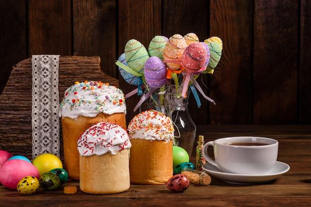 Pasen-cake en kleurrijke eieren met theekop Premium Foto