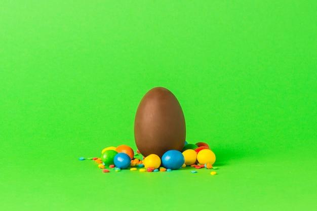 Pasen-chocolade-ei en multi gekleurde snoepjes op een groene ondergrond. vrolijk pasen-vieringsconcept. Premium Foto