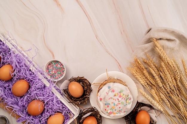 Pasen concept. bakken en koken. pasen cake ingrediënten op witte marmeren tafelblad weergave plat leggen met kopie ruimte Premium Foto
