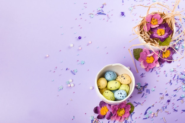 Pasen-decor in pastelkleuren. paaseieren, snoep, snoep, bloemen en eierschalen. Premium Foto