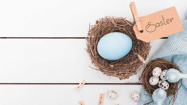 Pasen-inschrijving met blauw ei in nest Gratis Foto