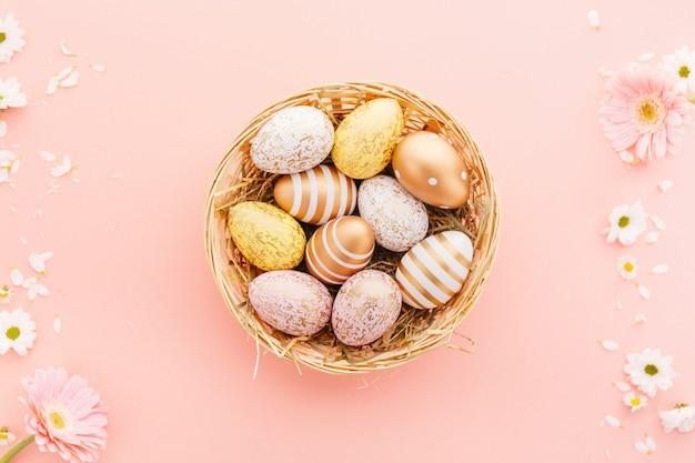 Pasen plat leggen van eieren met bloemen op roze Gratis Foto
