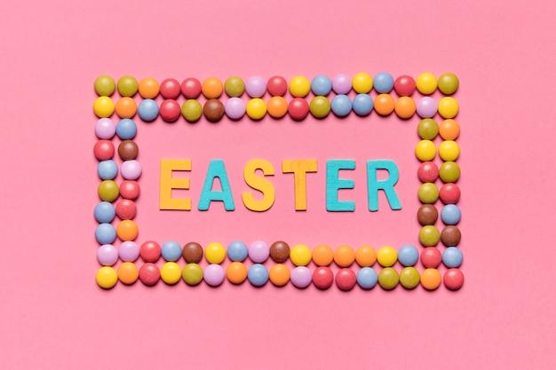 Pasen-woord binnen het kleurrijke kader van gemsuikergoed over de roze achtergrond Gratis Foto