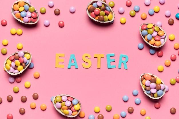 Pasen-woord dat met kleurrijke gemsuikergoed en paaseieren op roze achtergrond wordt omringd Gratis Foto