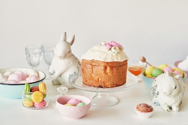 Pasen zoet brood, pasen cake en veelkleurige eieren met tulpen en een wit konijn. vakantie ontbijt concept met kopie ruimte. Premium Foto