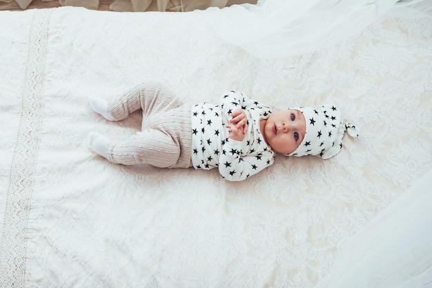 Pasgeboren baby gekleed in een wit pak en zwarte sterren is een wit zacht bed in de studio Premium Foto