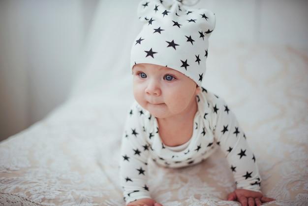 Pasgeboren baby gekleed in een wit pak en zwarte sterren is een wit zacht bed Premium Foto