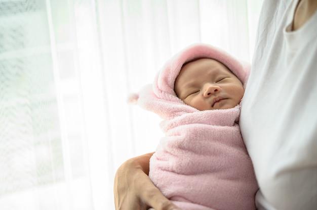 Pasgeboren baby slaapt in de omhelzing van de moeder Gratis Foto
