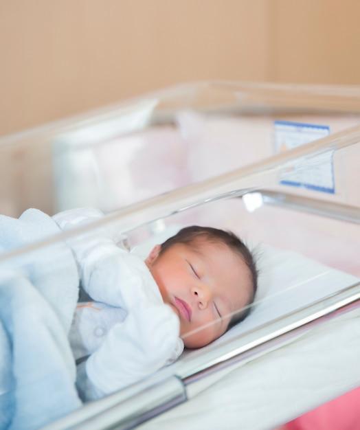 Pasgeboren baby slaapt in ziekenhuis wieg in pasgeboren kleding Gratis Foto