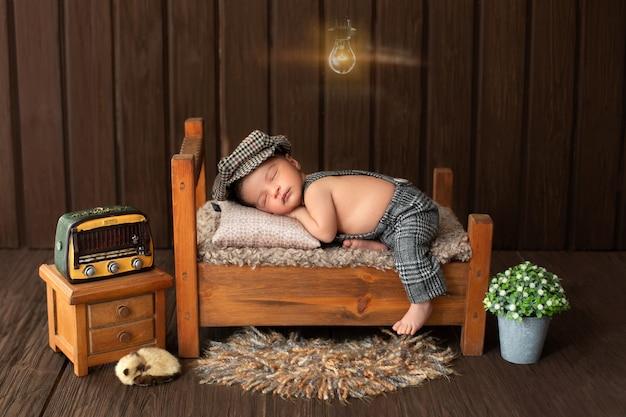 Pasgeboren babyportret van sympathieke en mooie babyjongen die op klein houten bed legt omringd door bloemenradio en leuk dier op vloer Gratis Foto