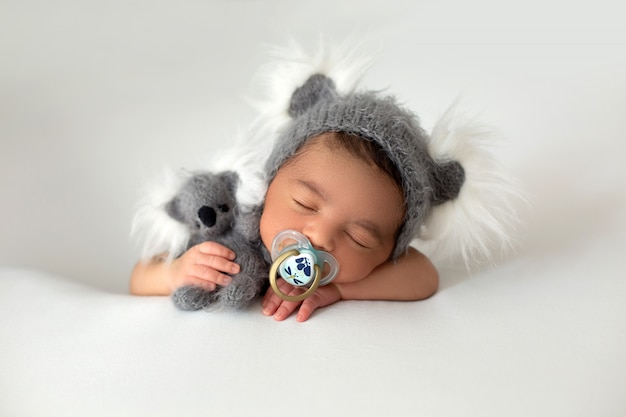 Pasgeboren schattige babyboy draagt weinig rustende baby met grijze hoed en grijs stuk speelgoed in zijn hand en fopspeen op zijn mond op een witte vloer Gratis Foto