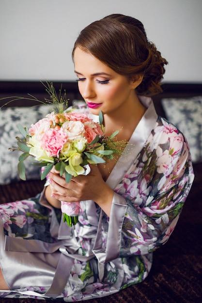 Pasgetrouwde mooie vrouw start voorbereiding van de huwelijksdag in bloemen badjas Gratis Foto