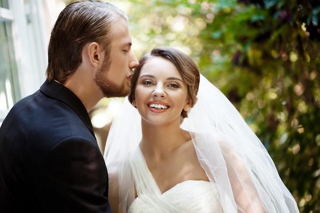 Pasgetrouwden in pak en trouwjurk glimlachen, zoenen in park. Gratis Foto