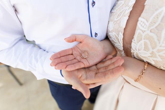 Pasgetrouwden met twee gouden trouwringen close-up. bruidspaar houden hun ringen. bruiloft. huwelijksceremonie Premium Foto