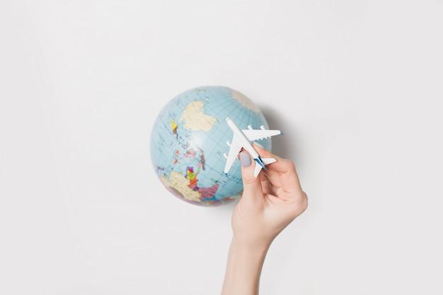 Passagiersvliegtuig in een vrouwelijke hand en een aardbol. vlucht concept Premium Foto