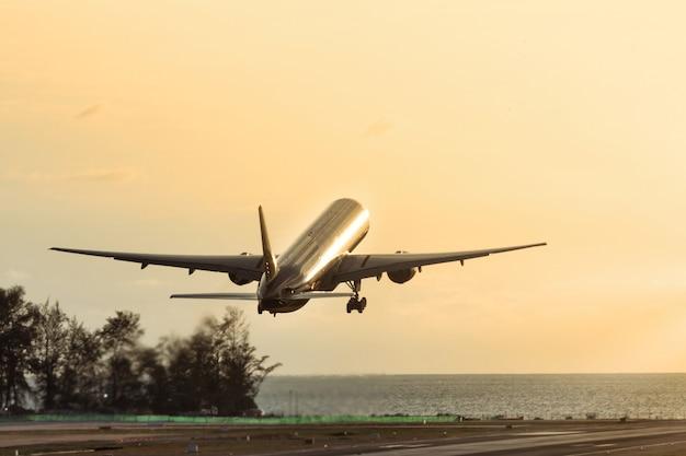 Passagiersvliegtuig opstijgen bij zonsondergang boven de zee. silhouet van vliegtuig vliegen omhoog. vakantie, luchtvaart, reisconcept Premium Foto