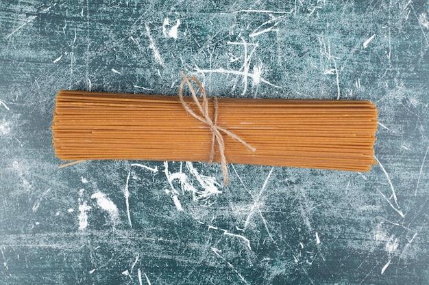 Pasta bos van volkoren spaghetti gebonden met touw op marmeren achtergrond. hoge kwaliteit foto Gratis Foto