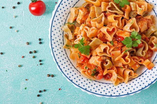 Pasta in de vorm van harten met kip en tomaten in tomatensaus. bovenaanzicht Gratis Foto