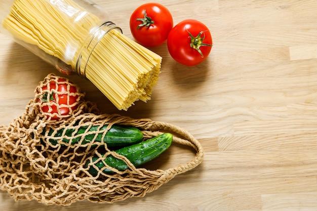 Pasta, komkommers en tomaten met netzak op een houten tafel Premium Foto