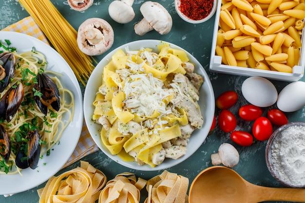 Pasta maaltijden in borden met rauwe pasta, tomaat, meel, champignons, eieren, kruiden, lepel Gratis Foto