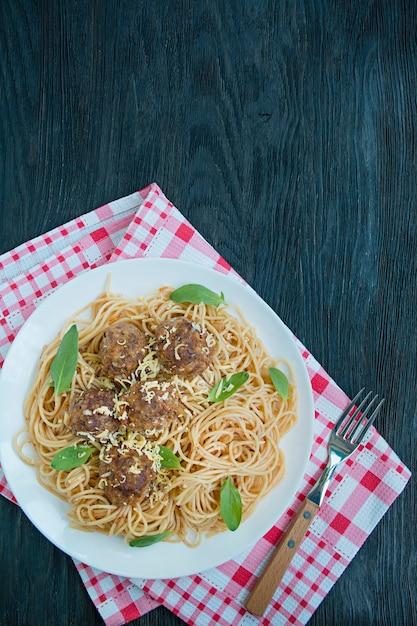 Pasta met gehaktballetjes en peterselie in tomatensaus. eettafel. tabel achtergrond menu. donkere houten achtergrond. bovenaanzicht ruimte voor tekst. Premium Foto
