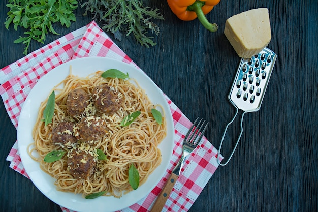 Pasta met gehaktballetjes en peterselie in tomatensaus. eettafel. tabel achtergrondmenu. donkere houten achtergrond. bovenaanzicht. ruimte voor tekst. Premium Foto