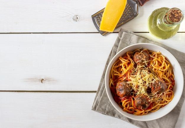 Pasta met gehaktballetjes en tomatensaus op een houten achtergrond. Premium Foto