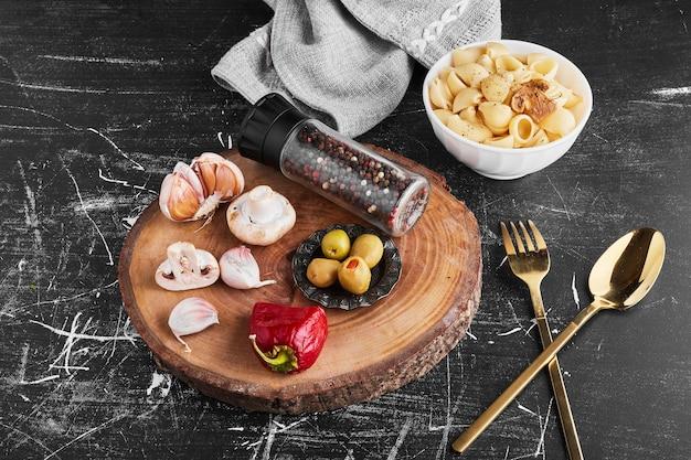 Pasta met ingrediënten op zwarte achtergrond. Gratis Foto