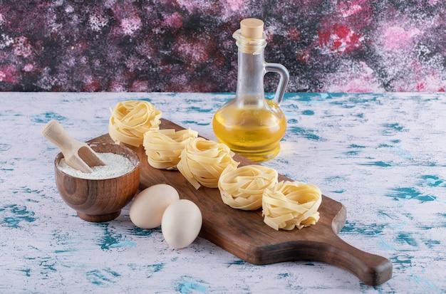 Pasta nesten op een houten bord met bloem, eieren en olijfolie. Gratis Foto
