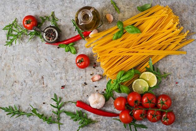 Pasta tagliatelle en ingrediënten voor het koken (tomaten, knoflook, basilicum, chili). bovenaanzicht Gratis Foto