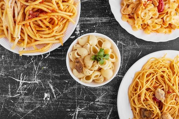 Pasta variëteiten in tomatensaus in een witte plaat op zwarte achtergrond. Gratis Foto