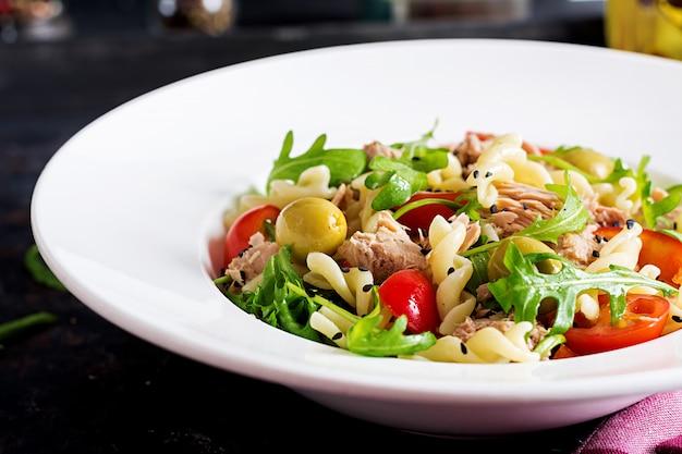 Pastasalade met tonijn, tomaten, olijven, komkommer, paprika en rucola op rustieke achtergrond. Premium Foto
