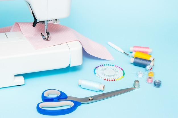 Pastelkleur achtergrond, naaister en designer bureau, handgemaakte accessoires. dradenrol, schaar en spelden. Premium Foto
