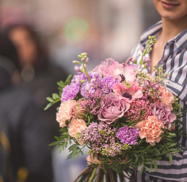 Pastelkleurig en lichtgekleurd bloemboeket omhelsd door een dame op straat Gratis Foto