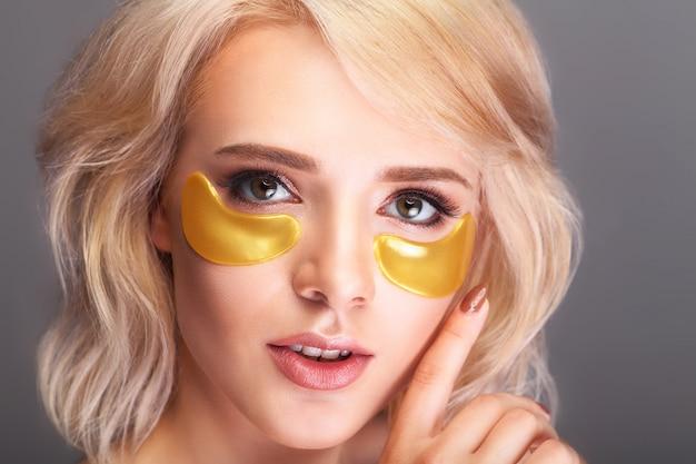 Patch onder de ogen. mooi vrouwengezicht met gouden hydrogelpleisters, opheffend antirimpelcollageenmasker. Premium Foto