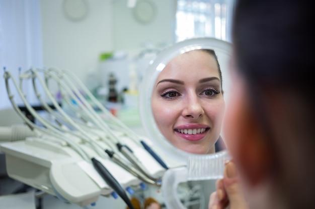 Patiënt die haar gezicht in spiegel bekijkt Gratis Foto