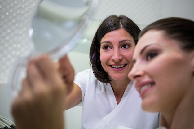Patiënt die haar tanden in spiegel controleert Gratis Foto