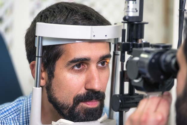 Patiënt in moderne oftalmologiekliniek die de oogvisie controleert. Premium Foto