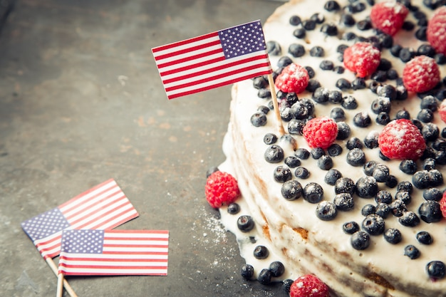 Patriottische amerikaanse vlagcake met bosbessen en aardbeien op uitstekende witte achtergrond Premium Foto