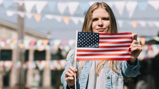Patriottische vrouw die de vlag van de vs toont bij festival Gratis Foto