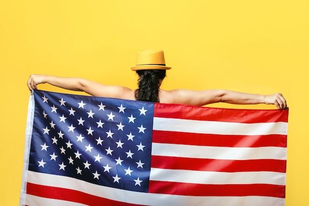 Patriottische vrouw met amerikaanse vlag. onafhankelijkheidsdag van de vs, 4 juli. vrijheidsconcept, uitzicht vanaf de achterkant. Premium Foto