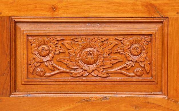 Patroon van bloem op houten achtergrond, thaise stijl wordt gesneden die Premium Foto